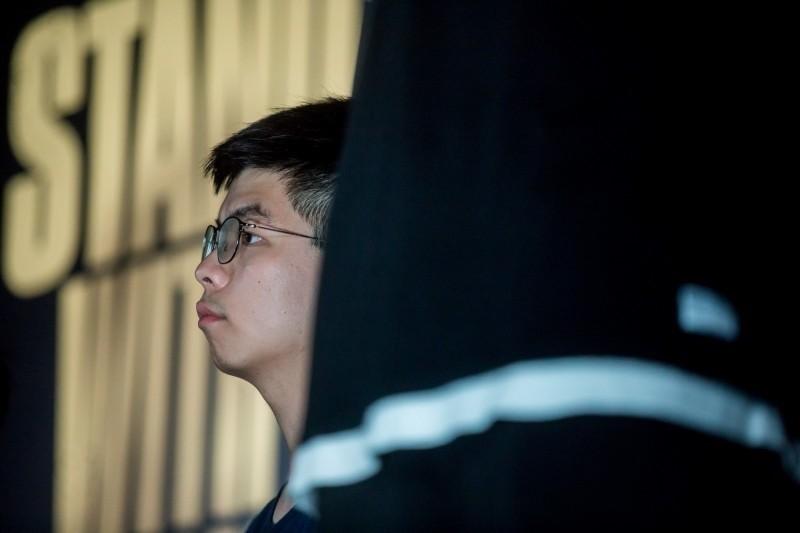 香港眾志秘書長黃之鋒今早前往海怡半島地鐵站途中,眾目睽睽下被押往灣仔警署總部,引發軒然大波。(彭博)