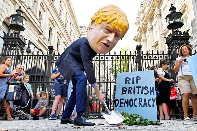 倫敦市示威民眾戴上首相強森的面具,地上立著寫有「安息吧 英國民主」的抗議標語。(法新社)