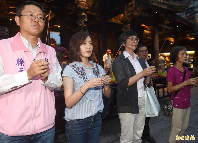 「學姊」黃瀞瑩(左二)今日傍晚在市府顧問蔡壁如(左三)陪同下,前往龍山寺參拜。(記者方賓照攝)