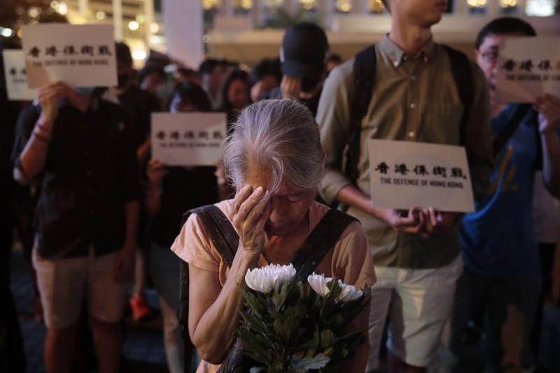 在「感謝勇武 X 重光紀念日」集會中,一名參加者手持白花及遮蓋右眼,對先前一名眼睛被港警射傷的女示威者致意。(美聯社)