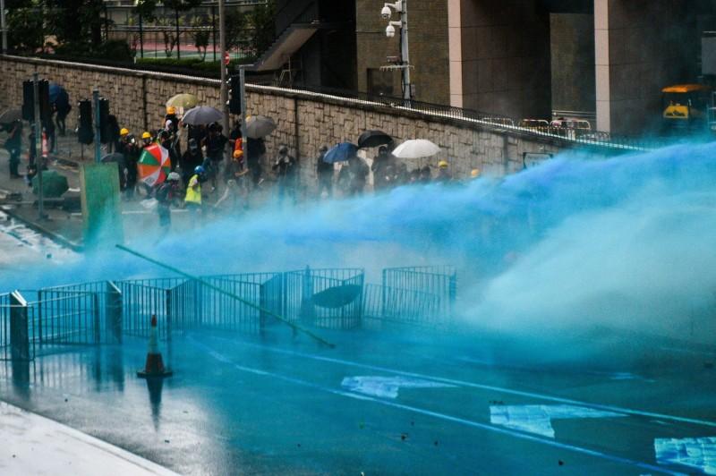 香港「民間人權陣線」今(31日)天發起的遊行雖然被警方攔阻,但港人仍自主發起聲稱屬宗教集會的「為香港罪人祈禱大遊行」,但遊行到晚間開始爆發衝突,香港警方出動水砲車噴射「藍色水柱」。(法新社)