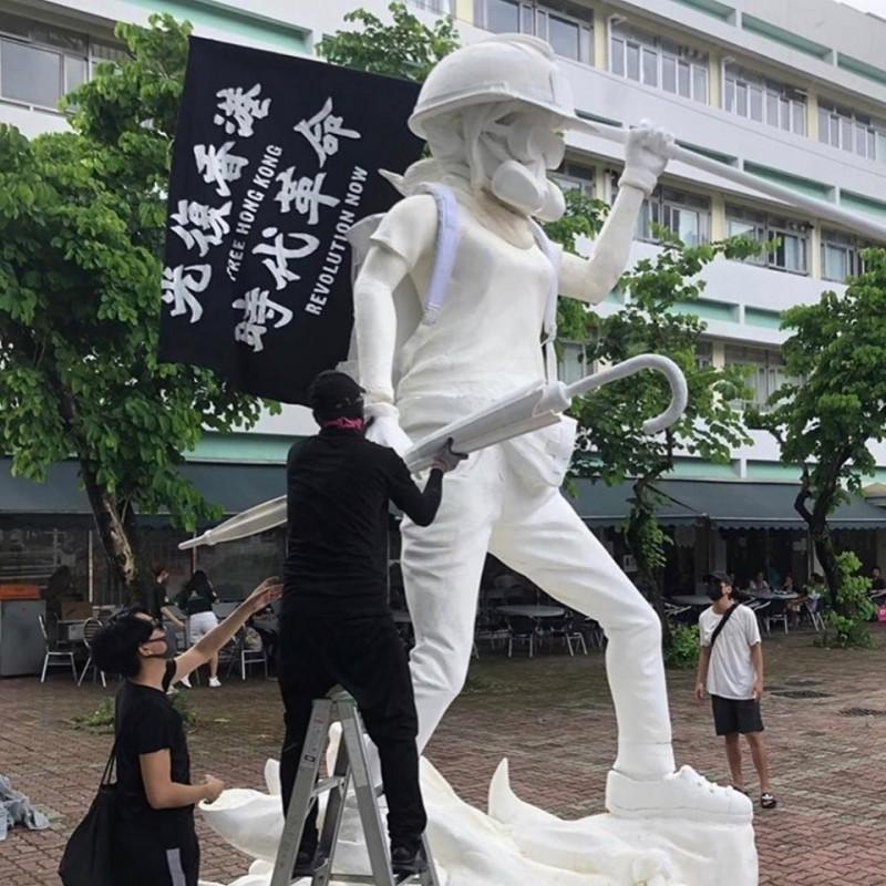 總長4公尺高的香港民主女神像,以反送中運動的女性前線抗爭者(勇武派)作為設計藍本,頸部以上戴著工地頭盔、防塵眼罩以及防毒面具,右手拿著一支用來防禦催淚彈的雨傘,左手則扛著一面寫有「光復香港、時代革命」的八字黑旗。(圖擷取自Facebook「范國威 Gary Fan」)