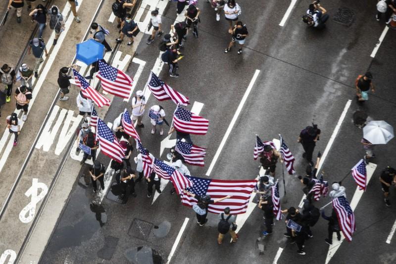 反送中示威者在路上揮舞著美國國旗、高唱美國國歌。(彭博)