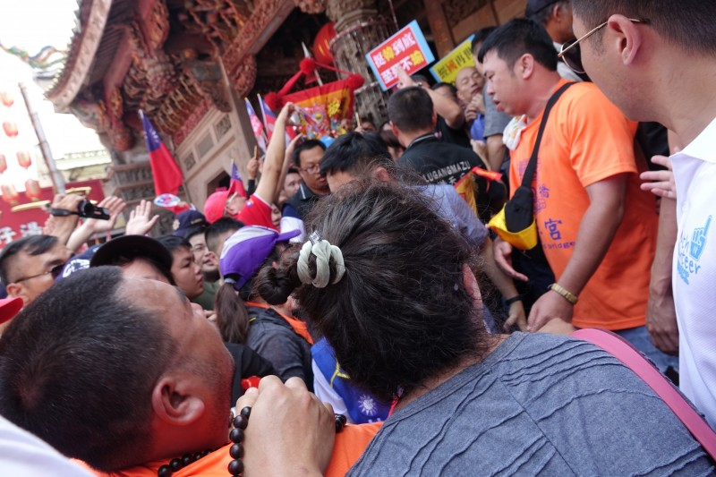 韓國瑜9月1日到鹿港天后宮參拜,畫面中他正備支持者包圍簇擁著步出宮門,正在門前的乩身(圖左下)整個人突然癱軟「退駕」了。(記者劉曉欣翻攝)