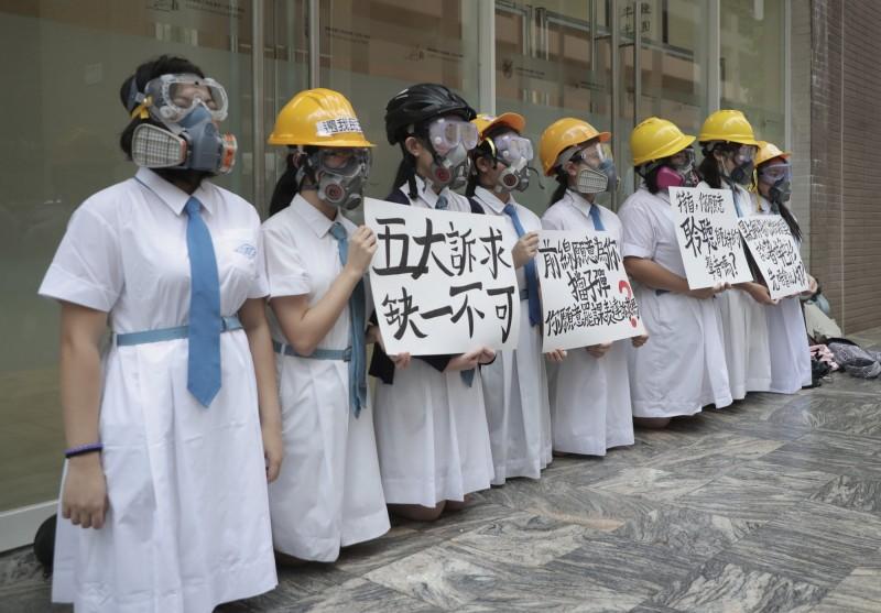 香港反送中延燒,嘉諾撒聖方濟各書院數名學生在校門前下跪,手舉標語,寫著「特首,你願意聆聽學妹的聲音嗎?」。(美聯社)