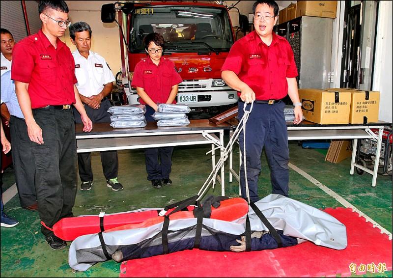 埔鹽消防分隊員宋明哲(右)示範打撈屍袋使用方式。(記者陳冠備攝)
