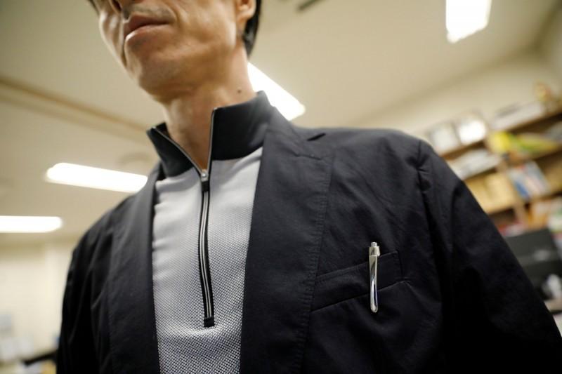 韓國職場霸凌嚴重,員工開始大量運用「間諜裝置」來蒐證,刺激了高科技錄影、錄音產品的市場。圖為男子在胸前口袋佩掛「間諜筆」。(路透)