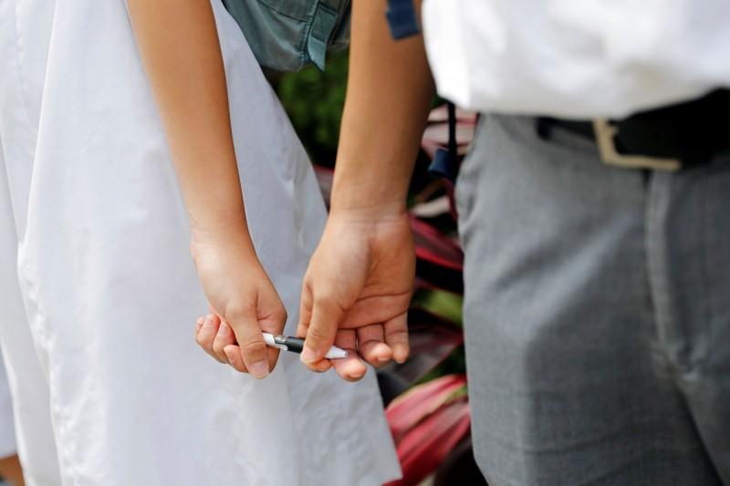 有網友發現,在人鏈之中有1男1女,疑似因不好意思牽手,所以一起握住一隻筆。(路透)