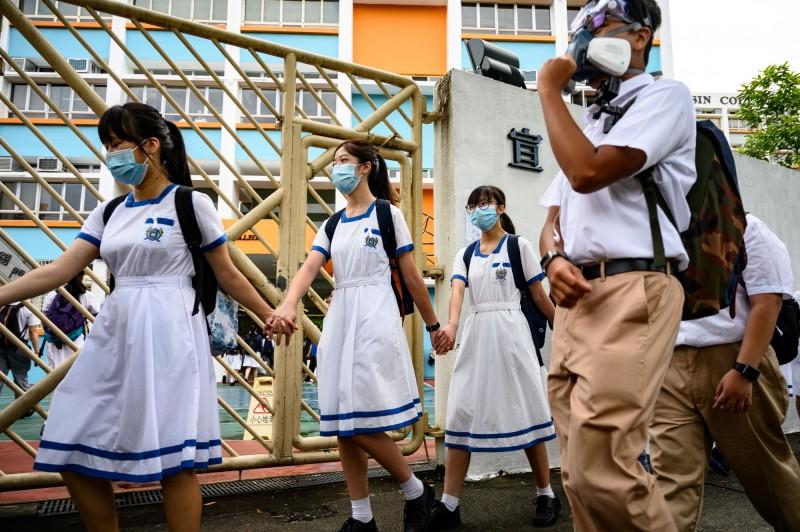 香港屯門4間中學校的學生今早牽手築起人鏈,聲援日前被警方上巴士逮捕的學生。(法新社)