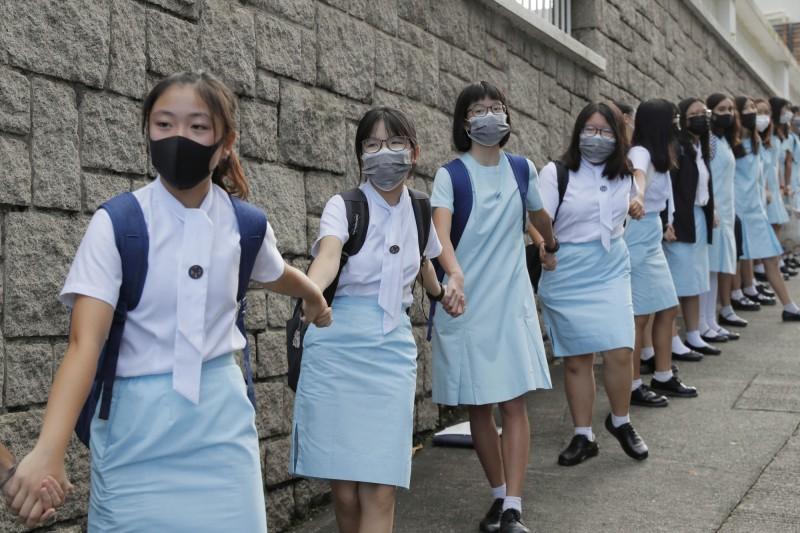 香港各地多所學校今早都有學生發起人鏈活動。圖為學生於瑪利諾修院學校外築起人鏈情形。(美聯社)