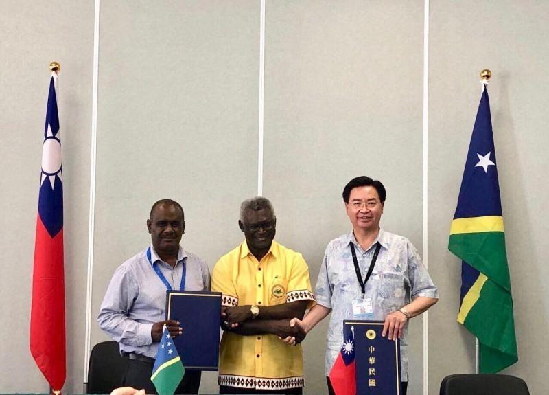 我太平洋友邦索羅門群島外長馬內列(左)明天訪台,圖為我國外交部長吳釗燮(右)8月時在索國總理蘇嘉瓦瑞(中)見證下,與索國外長馬內列簽訂台索免簽待遇協定的畫面。(外交部提供)