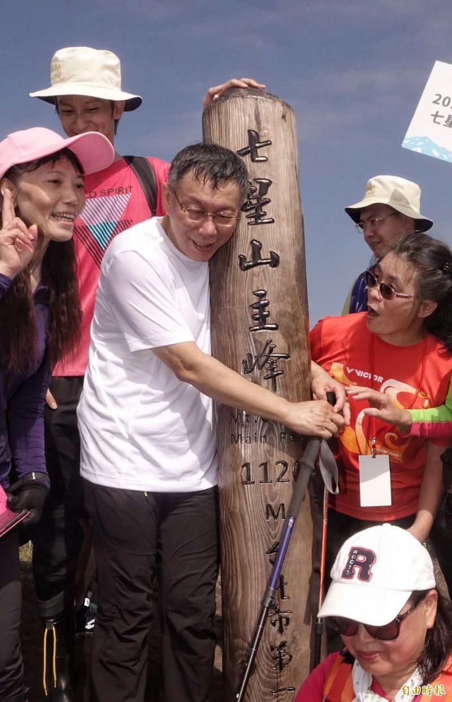 抵達七星山主峰,柯文哲一臉疲累,抱住木柱休息。(記者張嘉明攝)
