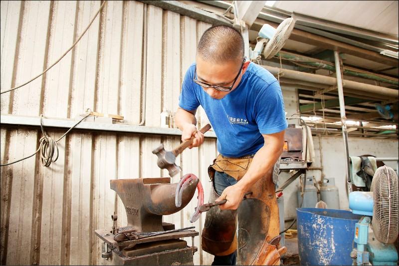 將馬蹄放入火爐燒紅後,用鉗子夾住蹄鐵放在鐵砧上,使用鍛槌幫蹄鐵塑形。(記者沈昱嘉/攝影)