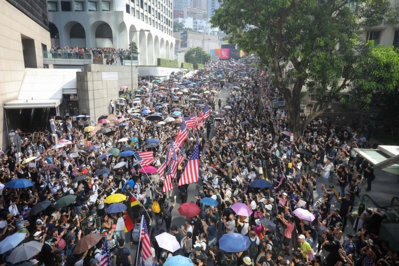 手持美國國旗的遊行隊伍持續在遮打花園與美國領事館之間的花園道繞行,沿路兩旁擠滿群眾。(法新社)