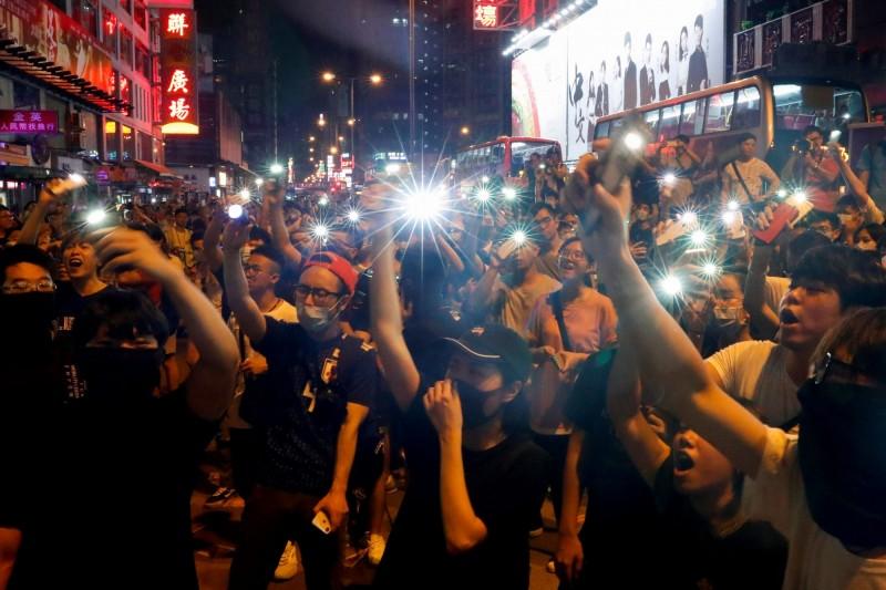 香港反送中,本月7日晚間示威在旺角警署外,以手機燈海、大合唱對抗警棍。(路透)