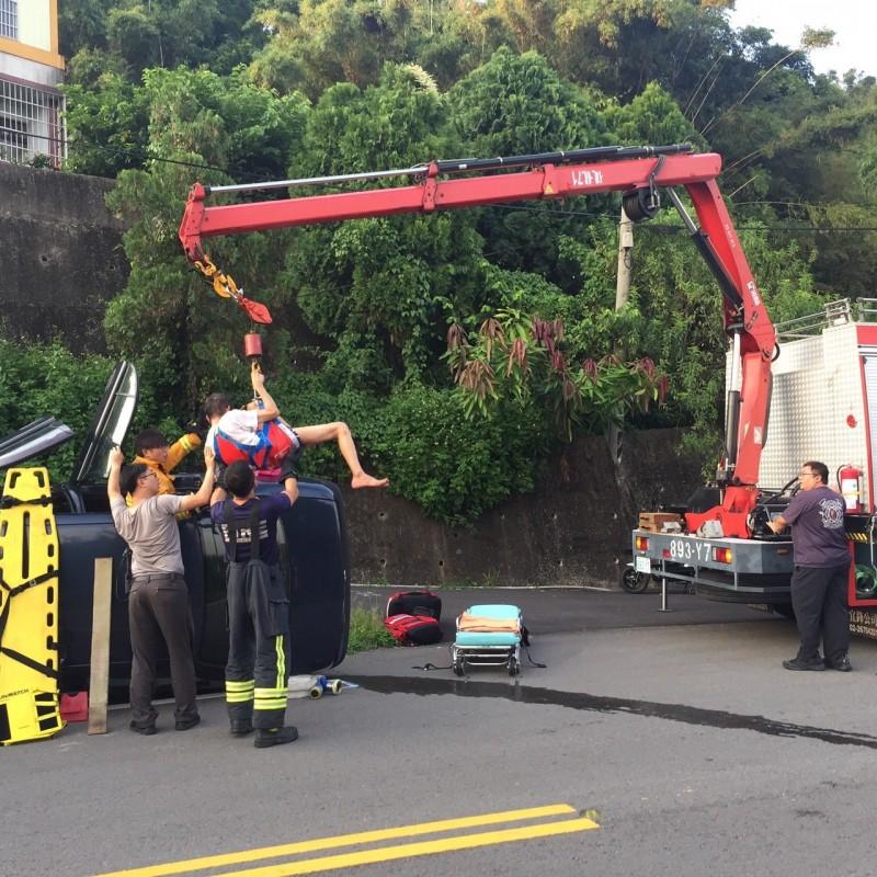 消防人員利用吊臂將傅男吊出送醫。(記者張勳騰翻攝)