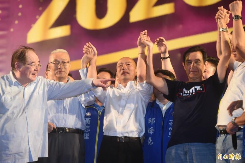 國民黨總統參選人韓國瑜(中)8日在新北市三重區舉行造勢大會,前總統馬英九(右)牽起韓國瑜的手象徵團結。(資料照)