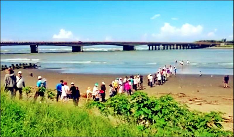 宗教團體50多人在鹽水溪畔違法放生螃蟹及魚類。(記者蔡文居翻攝)