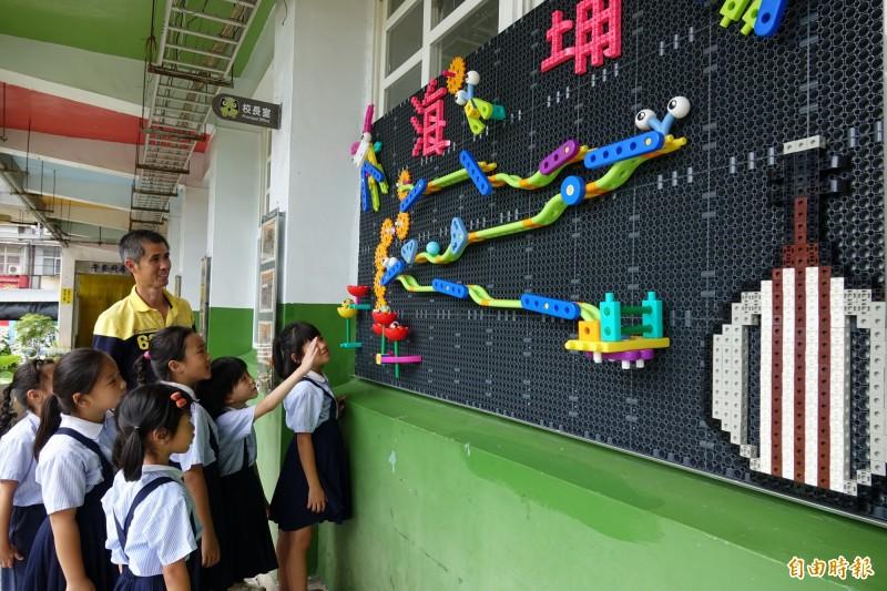 「球來了!」鹿港海埔國小全新的積木牆,校長施榕鑫帶著學生一起玩。(記者劉曉欣攝)