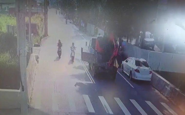 監視器拍到,大貨車行經霧峰福新路時,後車斗尾門突然鬆脫往左甩。(記者陳建志翻攝)