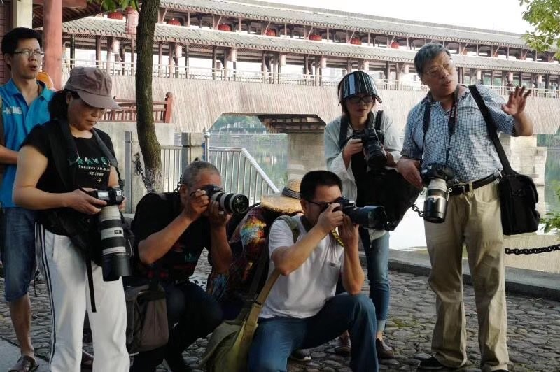 中國攝影師盧廣(右一)指導幾位攝影師拍攝技巧。(圖翻攝自徐小莉推特)