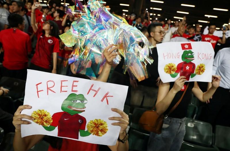 也有香港球迷舉著寫有「FREE HK」的趣味標語牌,支持示威者。(路透)