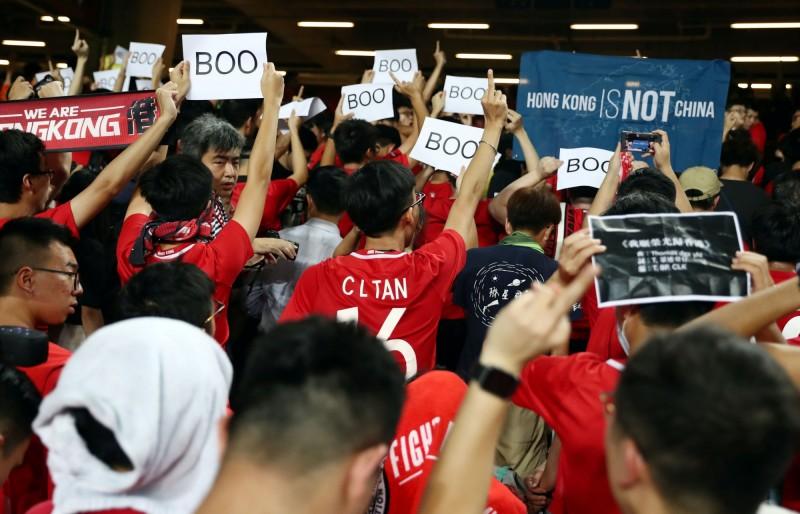 賽事開始前,會場內播放中共國歌,許多香港球迷高舉標語抱以噓聲。(路透)
