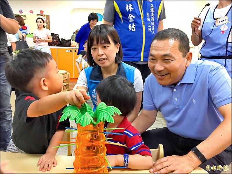 新北市土城區永豐公共托育中心昨天開幕,市長侯友宜(右)和小朋友們一起玩遊戲。(記者邱書昱攝)