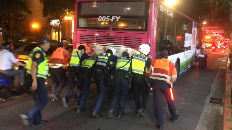 10多名員警義交及附近熱心民眾,將公車推往500公尺遠的路邊,排除交通打結。(記者姚岳宏翻攝)