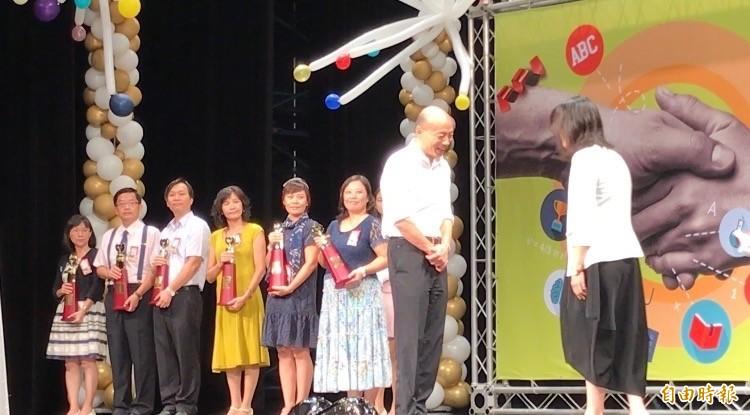 幼兒園長鄭淑蓮(右)上前領獎時未伸出手,韓國瑜兩手交疊在前、面帶微笑,兩人互相點頭致意。(記者洪臣宏攝)
