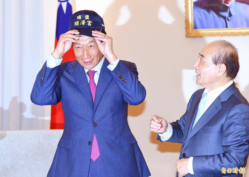 Chinese Nationalist Party (KMT) Legislator Wang Jyn-pyng, right, presents Hon Hai Precision Industry Co founder Terry Gou with a baseball cap from Changhua County's Puyan Shunze Temple as the two men exchange gifts at Wang's office at the Legislative Yuan in Taipei yesterday. Photo: Liao Chen-huei, Taipei Times