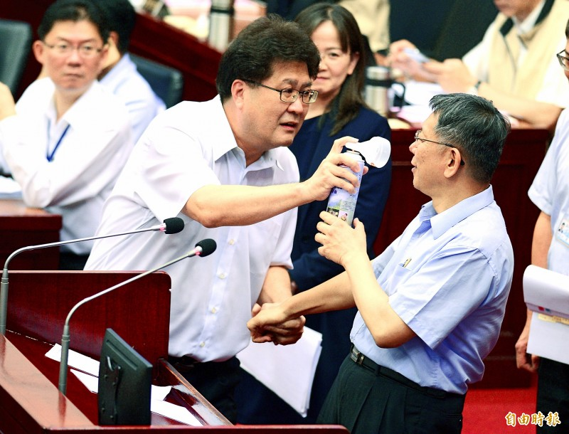 Democratic Progressive Party Taipei City Councilor Lin Shih-tsung, left, aims the nozzle of an air horn at Taipei Mayor Ko Wen-je yesterday as Ko visits the Taipei City Council to give a report. Photo: Wang Yi-sung, Taipei Times