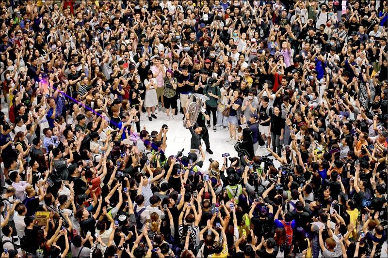 香港「反送中」示威者11日晚間在沙田新城市廣場等地,舉起手機亮起燈光,高唱抗爭新主題曲《願榮光歸香港》,還有人現場演奏低音號。(法新社)