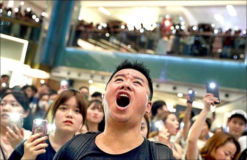 香港「反送中」示威者11日晚間在沙田新城市廣場等地,舉起手機亮起燈光,高唱抗爭新主題曲《願榮光歸香港》,還有人現場演奏低音號。(路透)