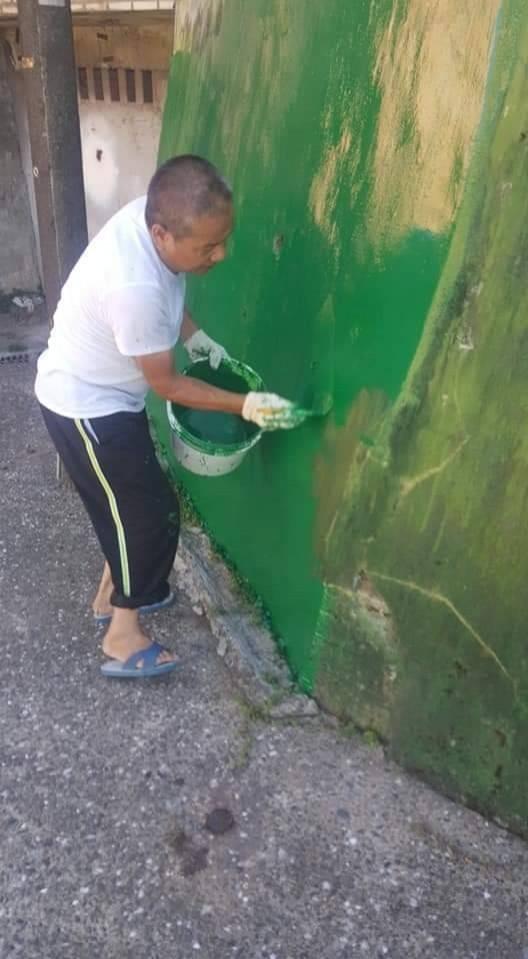 基隆市新西里長陳漢昭,自費購買油漆粉刷里內圍牆,打造綠色家園。(記者俞肇福攝)