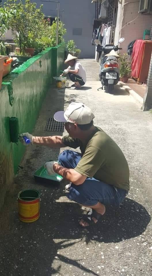 基隆市新西里長陳漢昭,自費購買油漆粉刷里內圍牆,打造綠色家園;感動里內鄰長、早起會會長等人加入刷油漆志工行列。(記者俞肇福翻攝)