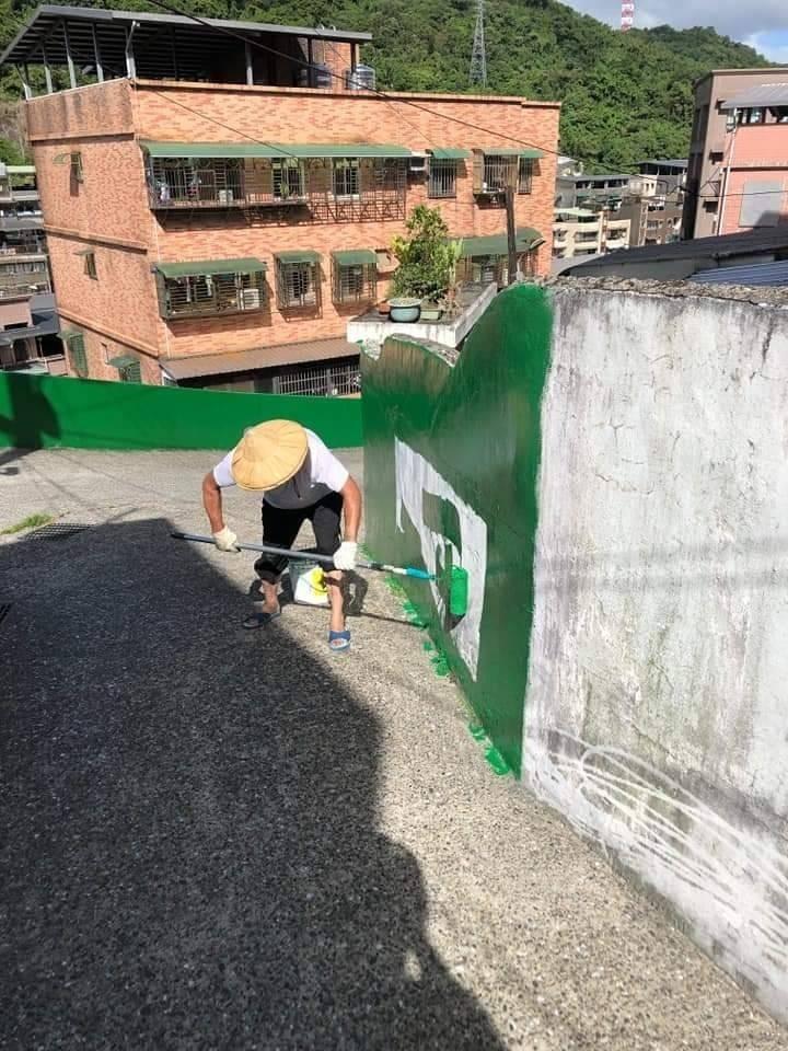 基隆市新西里長陳漢昭,自費購買油漆粉刷里內圍牆,打造綠色家園;陳漢昭的精神感動里民來協助。(記者俞肇福翻攝)