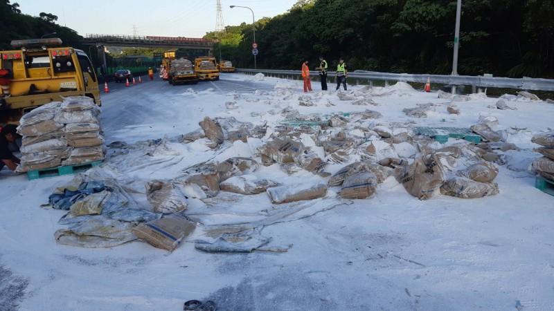 載滿水泥包的貨車在國道3號汐止段南下匝道翻覆,水泥包散落佔用車道,嚴重影響交通。(圖由新北市交通局提供)