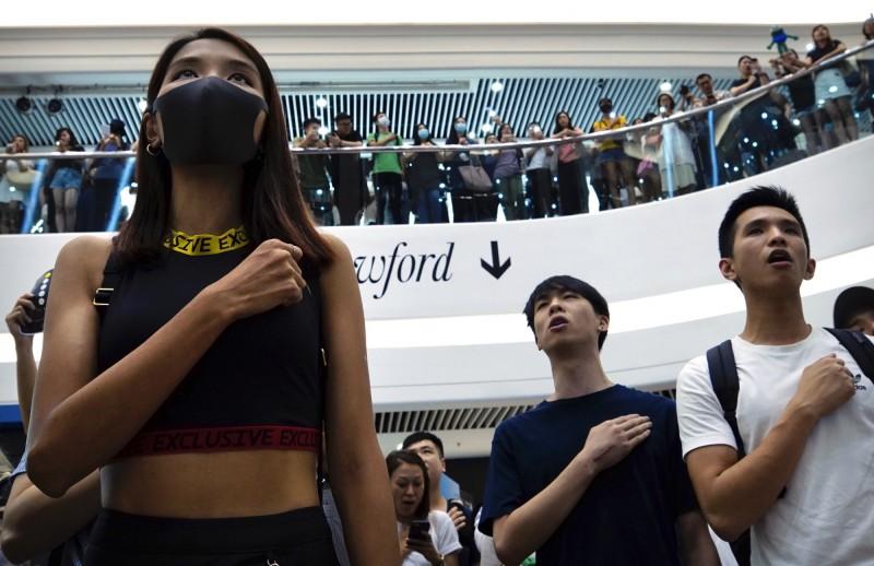 近來越來越多人在唱《願榮光歸香港》時,將右手放至於左胸。圖為銅鑼灣的時代廣場。(美聯社)