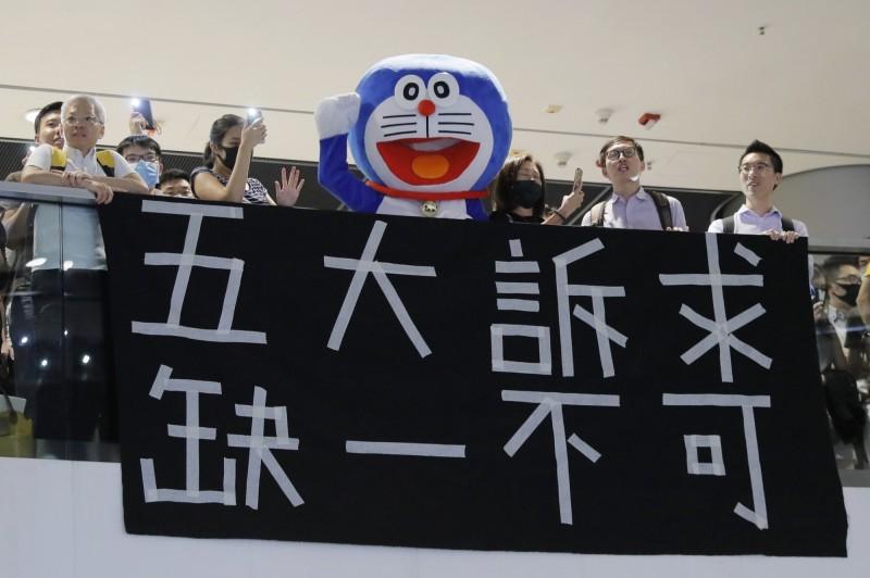 IFC現場有人掛出「五大訴求 缺一不可」的布條,也有人穿上知名動畫腳色的布偶。(美聯社)