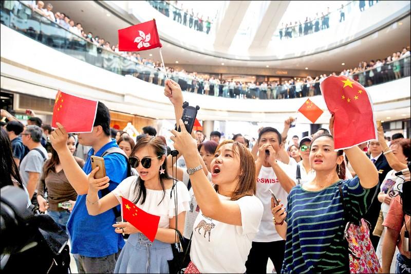 支持中、港政府的人士揮舞「五星旗」、「洋紫荊旗」,唱中國國歌。(路透)