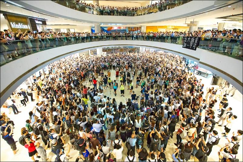 香港中西區中環「國際金融中心」(IFC)的中庭,十二日先後有支持北京和港府的人士,以及支持「反送中」的市民,聚集高唱中國國歌「義勇軍進行曲」與「願榮光歸香港」,用歌聲「拚場」。(歐新社)