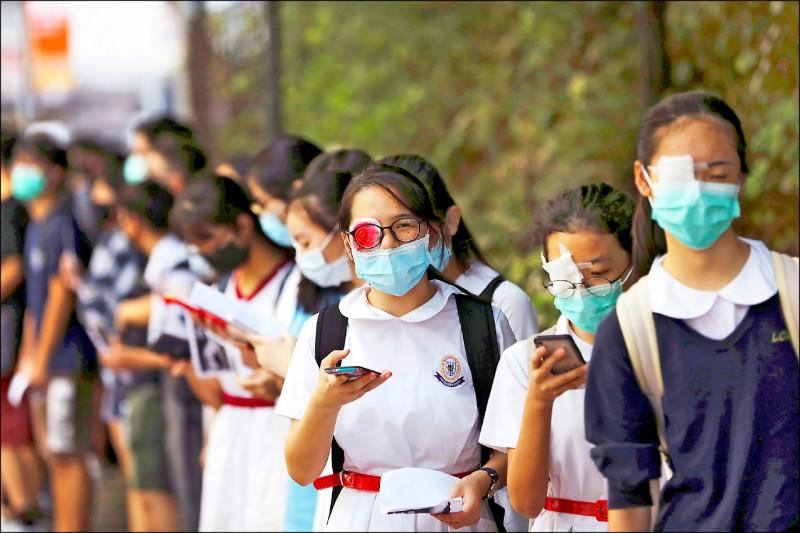 中學生除穿校服與戴口罩,有人還戴防毒面具,並以右眼貼紗布的方式,抗議八月十一日一名女示威者的右眼疑似遭港警用「布袋彈」打爆。(路透)