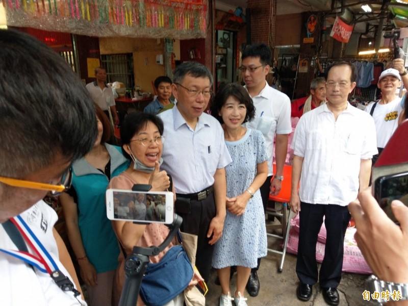 柯文哲及太太陳佩琪到三民市場吃麵羹,支持者爭相與他們合照。(記者方志賢攝)