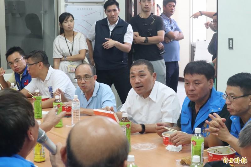 侯友宜會後與里長、工程人員一同吃便當,感謝他們犧牲假期辛苦付出。(記者周湘芸攝)