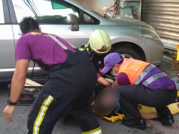 消防人員將夾在鐵捲門下的甘姓婦人,緊急送醫後仍傷重不治。(消防局提供)