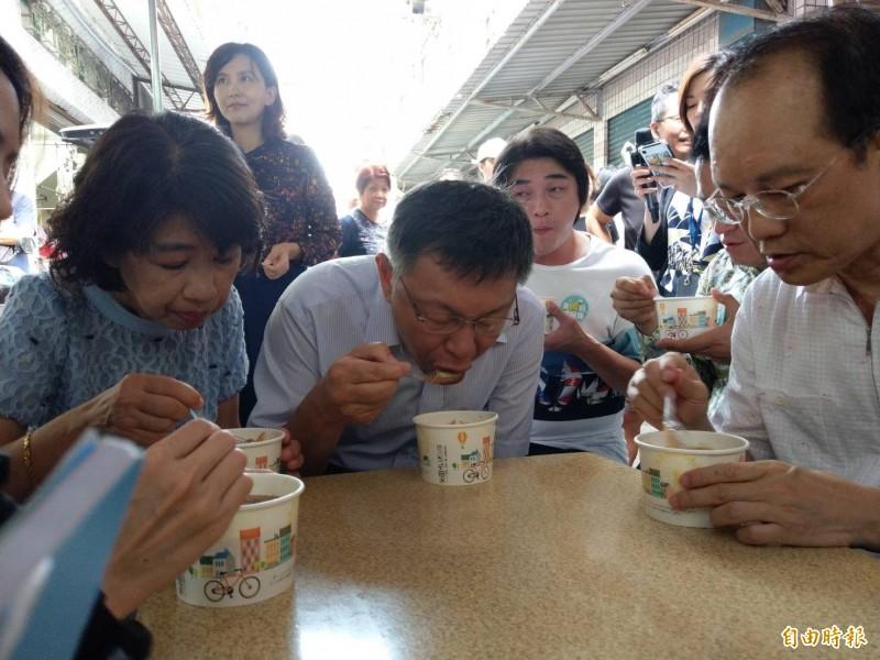 柯文哲(中)及太太陳佩琪(左)到三民市場吃熱騰騰麵羹。(記者方志賢攝)