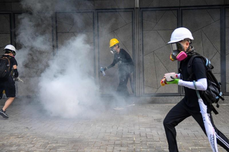 警方施放催淚煙,示威者嘗試以水澆熄。(法新社)