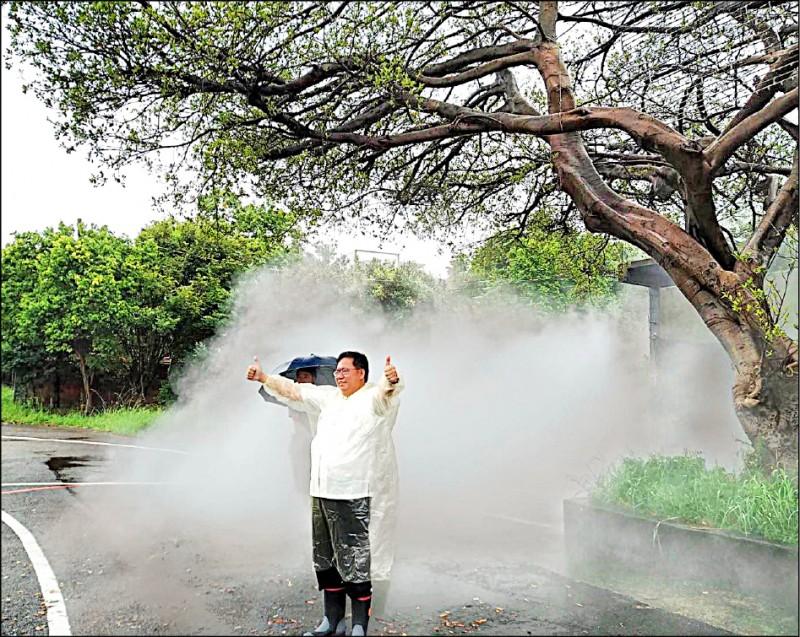 鄭文燦在藝術品「共用循環」的水霧中,與民眾一起拍下美照。(記者陳恩惠翻攝)