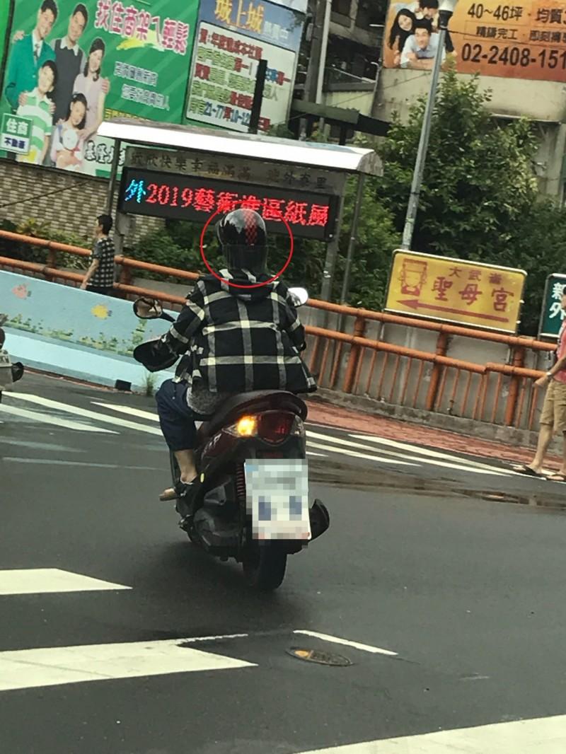 網友拍下婦人將安全帽反戴的照片(記者吳昇儒翻攝)